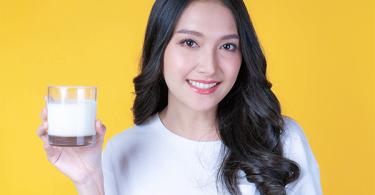 亚洲妇女拿着一杯牛奶