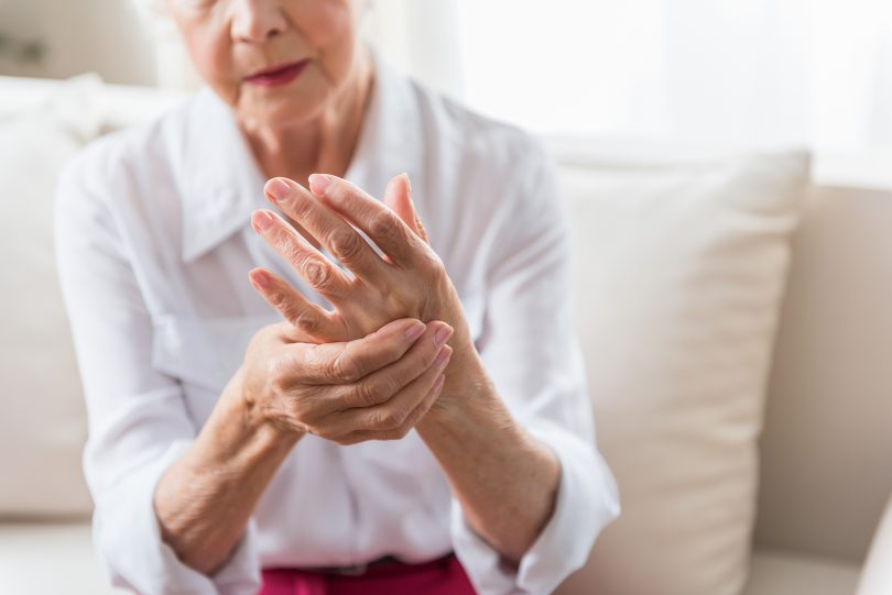 Woman massages hands to relive joint pain.