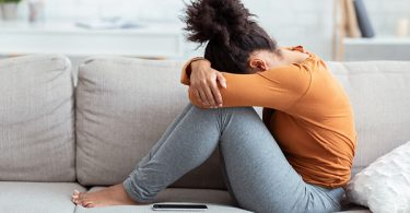 Young woman depressed on sofa