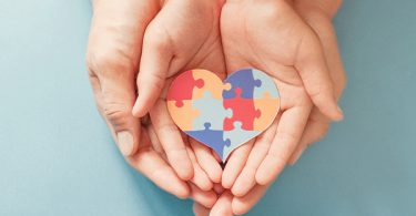 Adult holding child hand with autism puzzle pieces