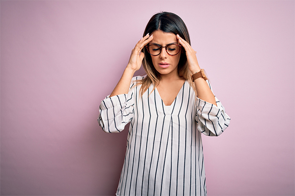 Young woman holding her face because she has a migraine