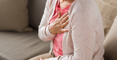 Older woman sitting on sofa with hand over heart.