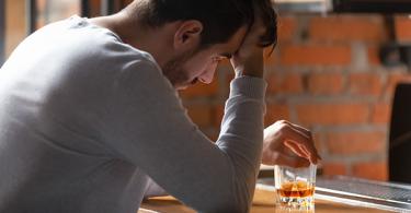 Sad man at the bar with alcohol