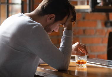 Sad man at the bar with alcohol