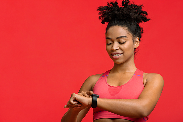 Black woman looking at wearable tracker after exercising