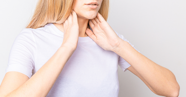 Woman holding thyroid glands on her neck