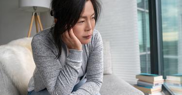 Older Asian woman sitting at home sad