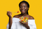 Black woman smiling and eating bowl of fruit