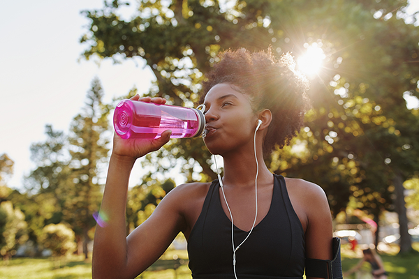 Black woman drinking water after run