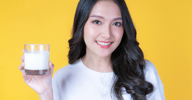 Asian woman holding a glass of milk